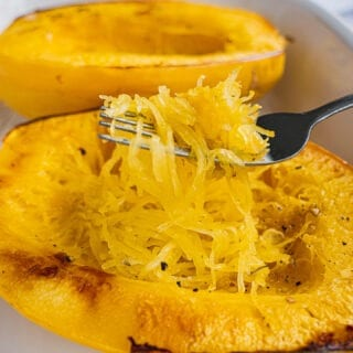 Two baked Spaghetti Squash on a baking dish. There is a fork shredding Spaghetti Squash into strands.