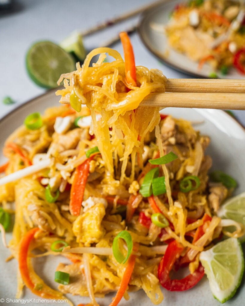 A pair of chopsticks are holding up some spaghetti squash pad thai.