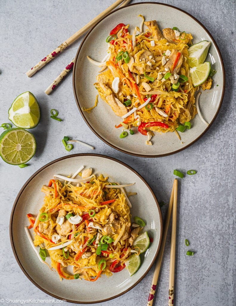 Two plates of pad thai noodles garnished with bean sprouts, lime, and green onion. There are two pairs of chopsticks on the side.