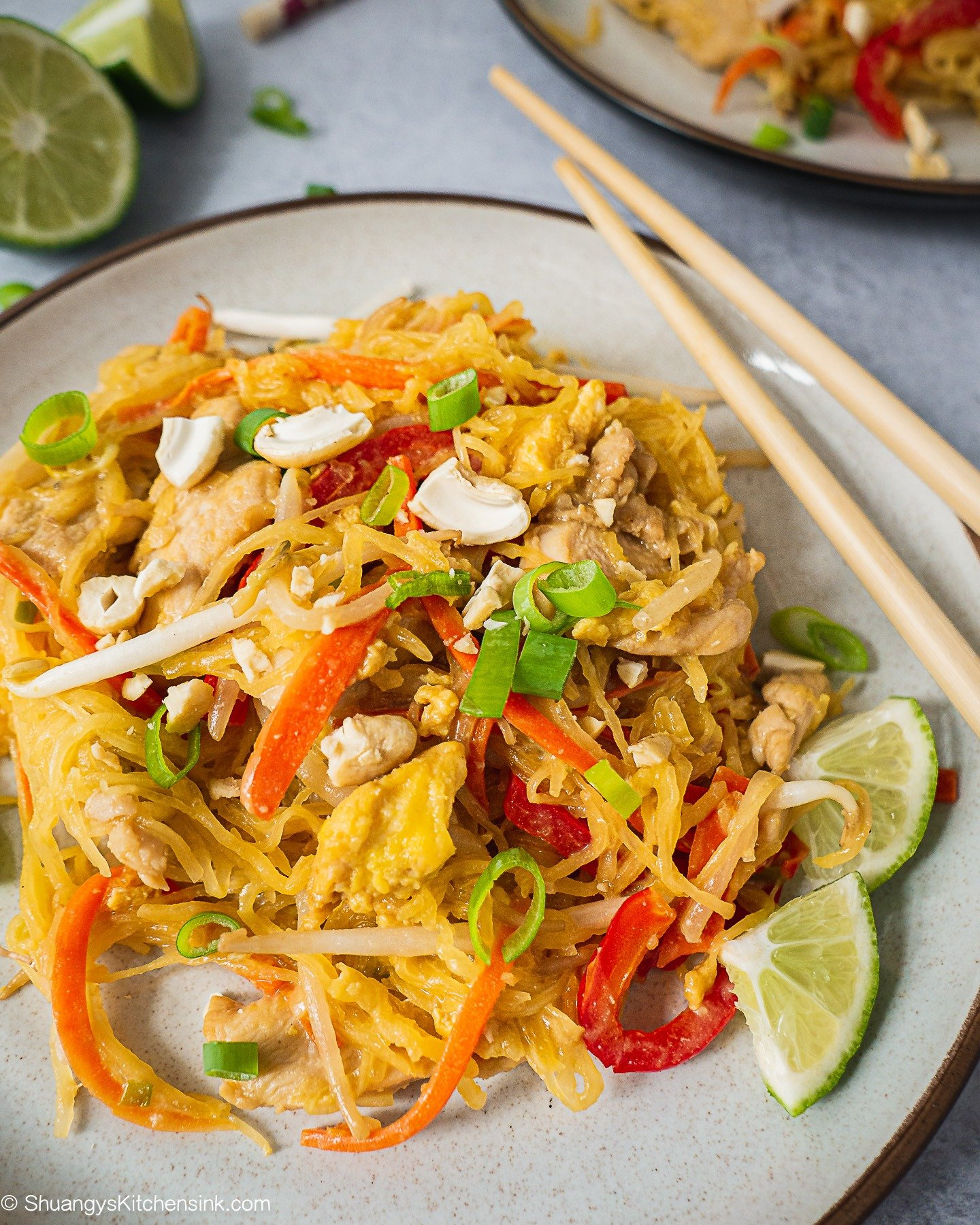 A plate of Chicken Pad Thai Noodles with crushed cashews on top. There are some fresh lime on the side. A pair of chopsticks and another plate in the back.