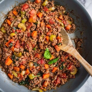 A pan of fresh and cooked bolognese sauce. There are carrots, celery and ground meat. There are some fresh basil on top.
