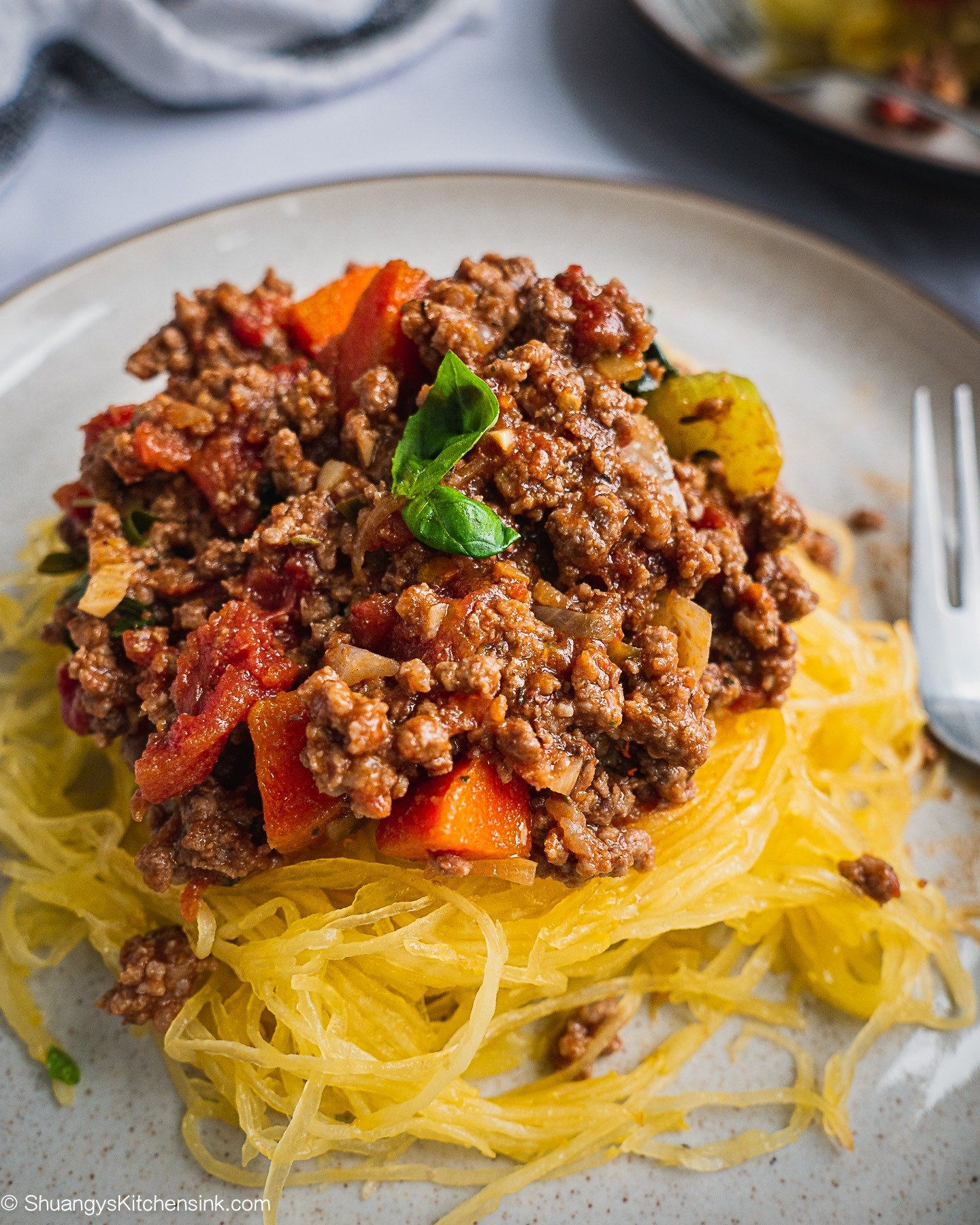A plate of spaghetti squash topped with bolognese sauce and fresh basil.