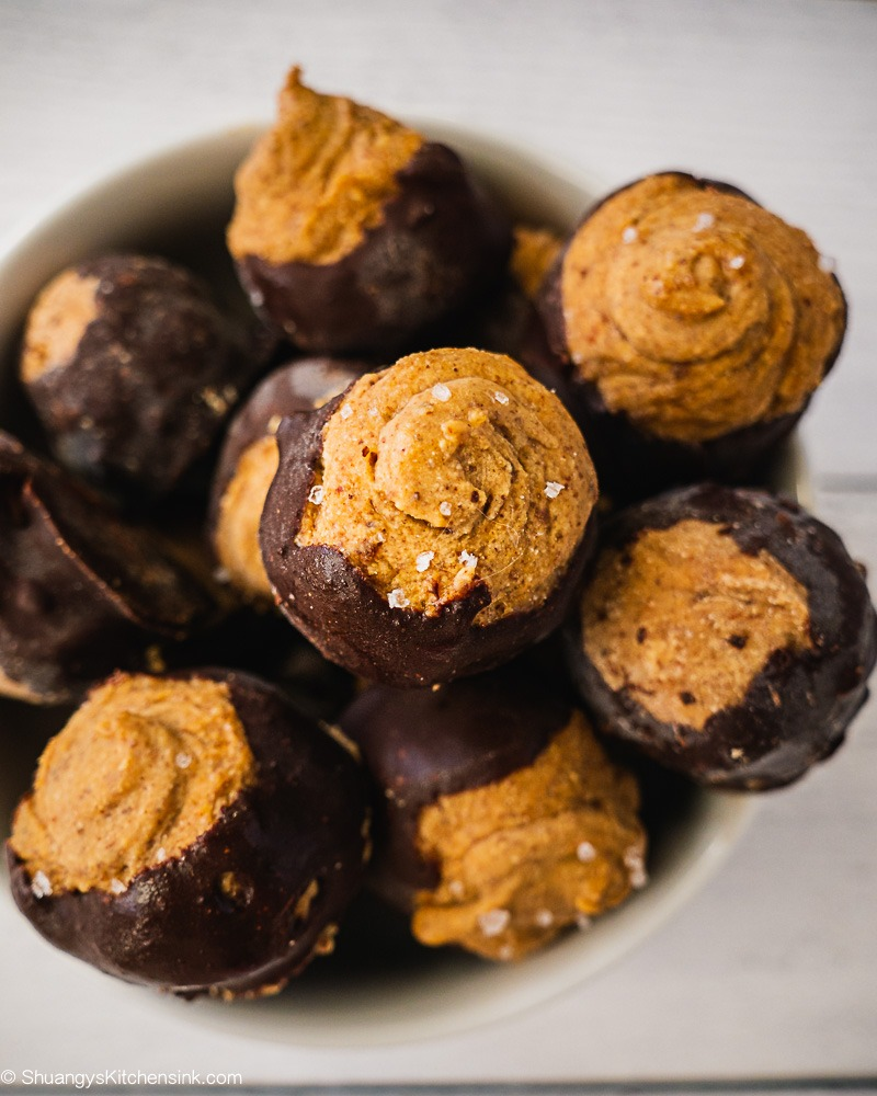 A bowl of Buckeye Balls with Chocolate covered on the bottom with a little bit of sea salt on top.