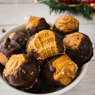A bowl of Buckeye Balls with Chocolate covered on the bottom with a little bit of sea salt on top. The one on top has a bite.