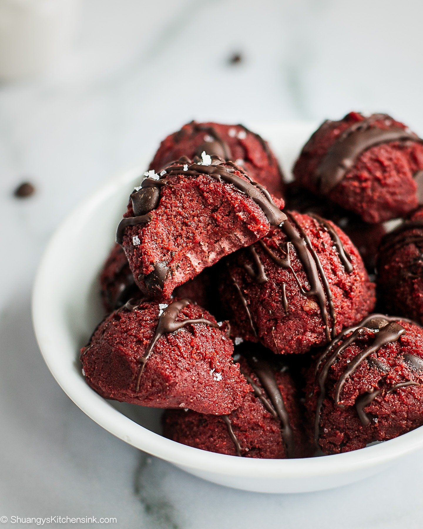 A bowl of red velvet cookie dough bites. There is a bite on the one on top.