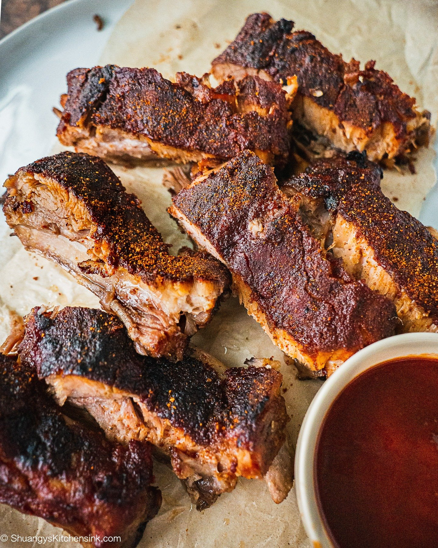 Charred Slow Cooker Whole30 BBQ Ribs on a piece of parchment paper. There is a jar of BBQ Sauce on the side.