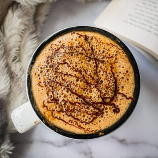 A mug of homemade mocha Latte with melted chocolate on top and sprinkle of cinnamon. It is very frothy.