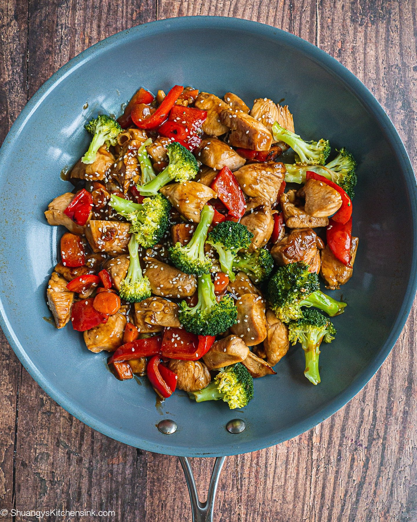 A pan of teriyaki chicken stir fry with broccoli and bell pepper.