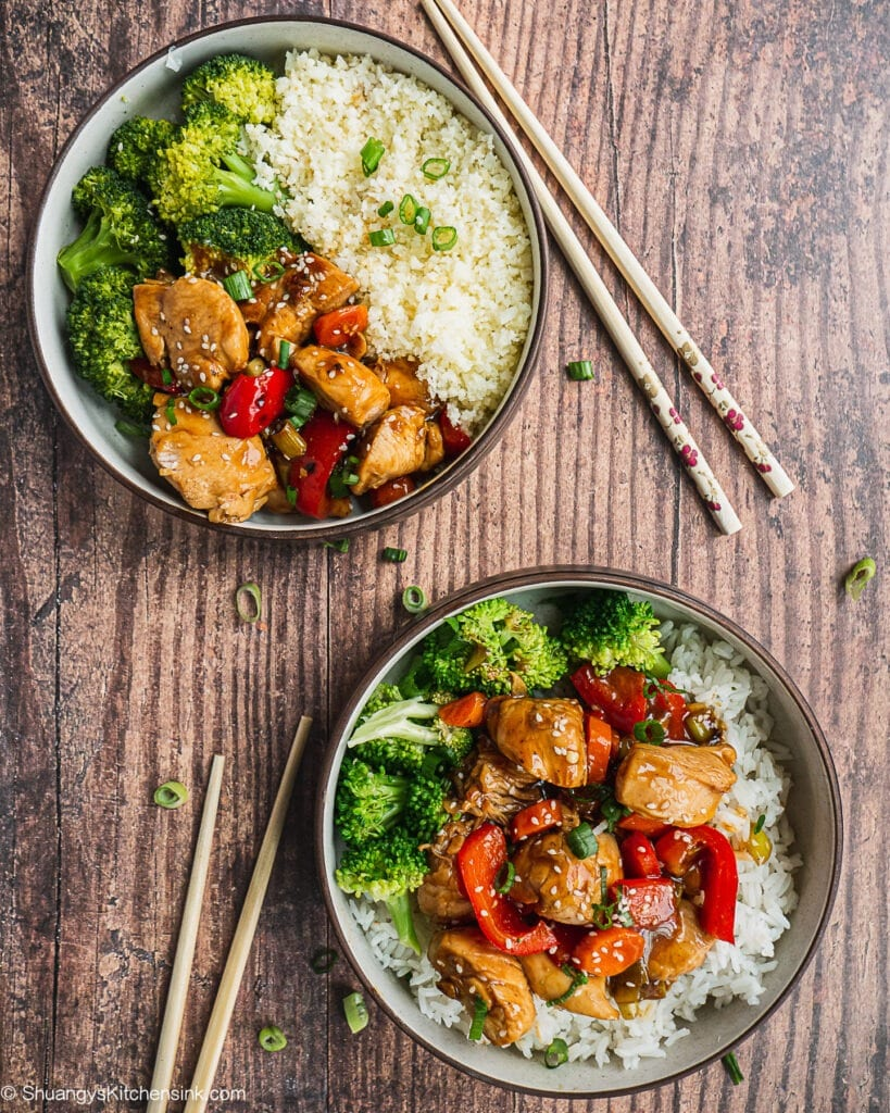 Two bowls of teriyaki chicken stir fry with broccoli. There are two pairs of chopstick on the side.
