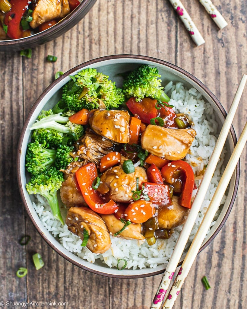 A bowl of teriyaki chicken stir fry with broccoli. There is a pair of chopstick on the side.