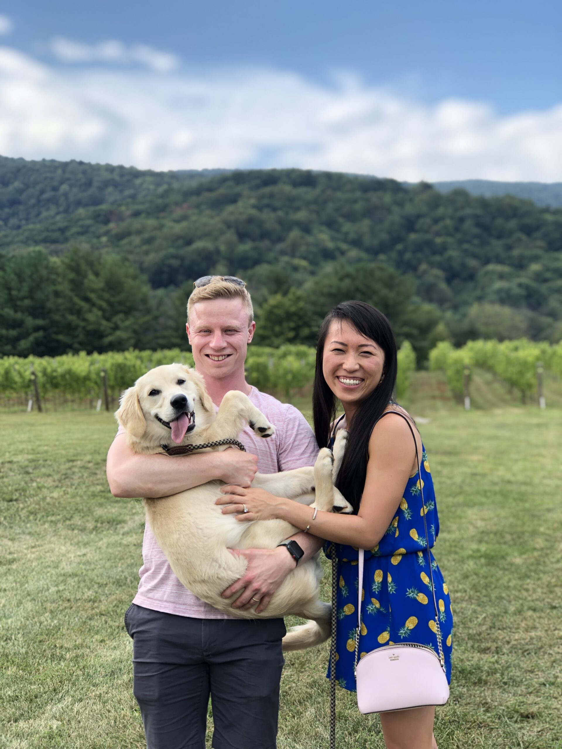 Tom and Shuang holding their Golden Retriever Muffin in front of a mountain