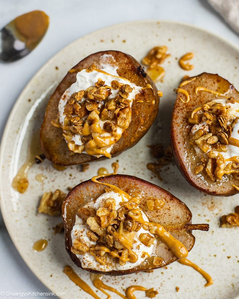 A plate of whole baked pears stuffed with vegan yogurt, granola, honey and walnuts and nut butter. Oven baked pears are spiced with cinnamon.
