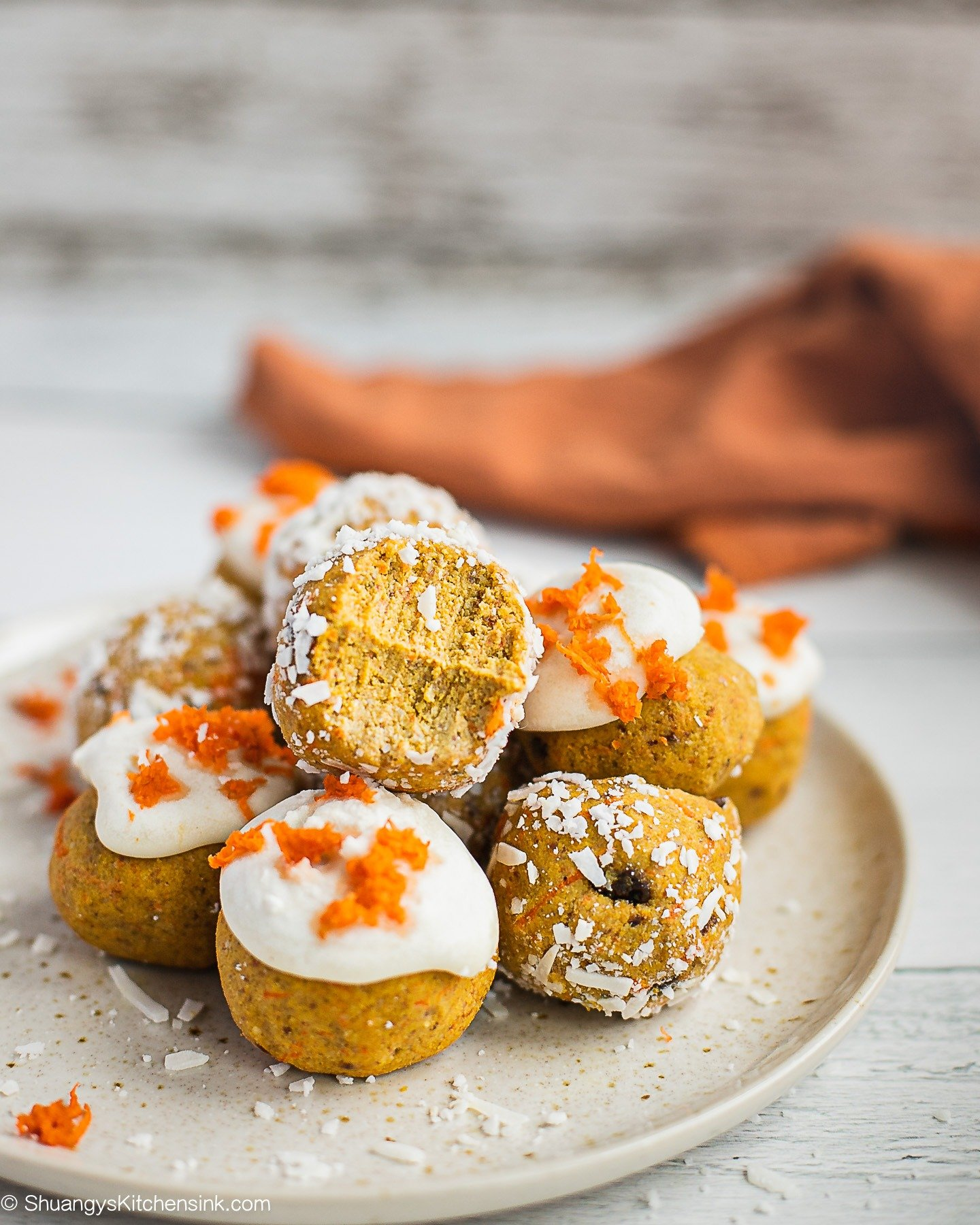 A plate of Carrot Cake truffles. A few of them are covered by coconut flakes, a few are covered by coconut butter and topped with shredded carrots.