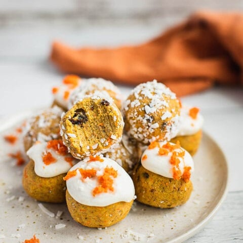 A plate of Carrot Cake truffles. A few of them are covered by coconut flakes, a few are covered by coconut butter and topped with shredded carrots. There is a bite on top.