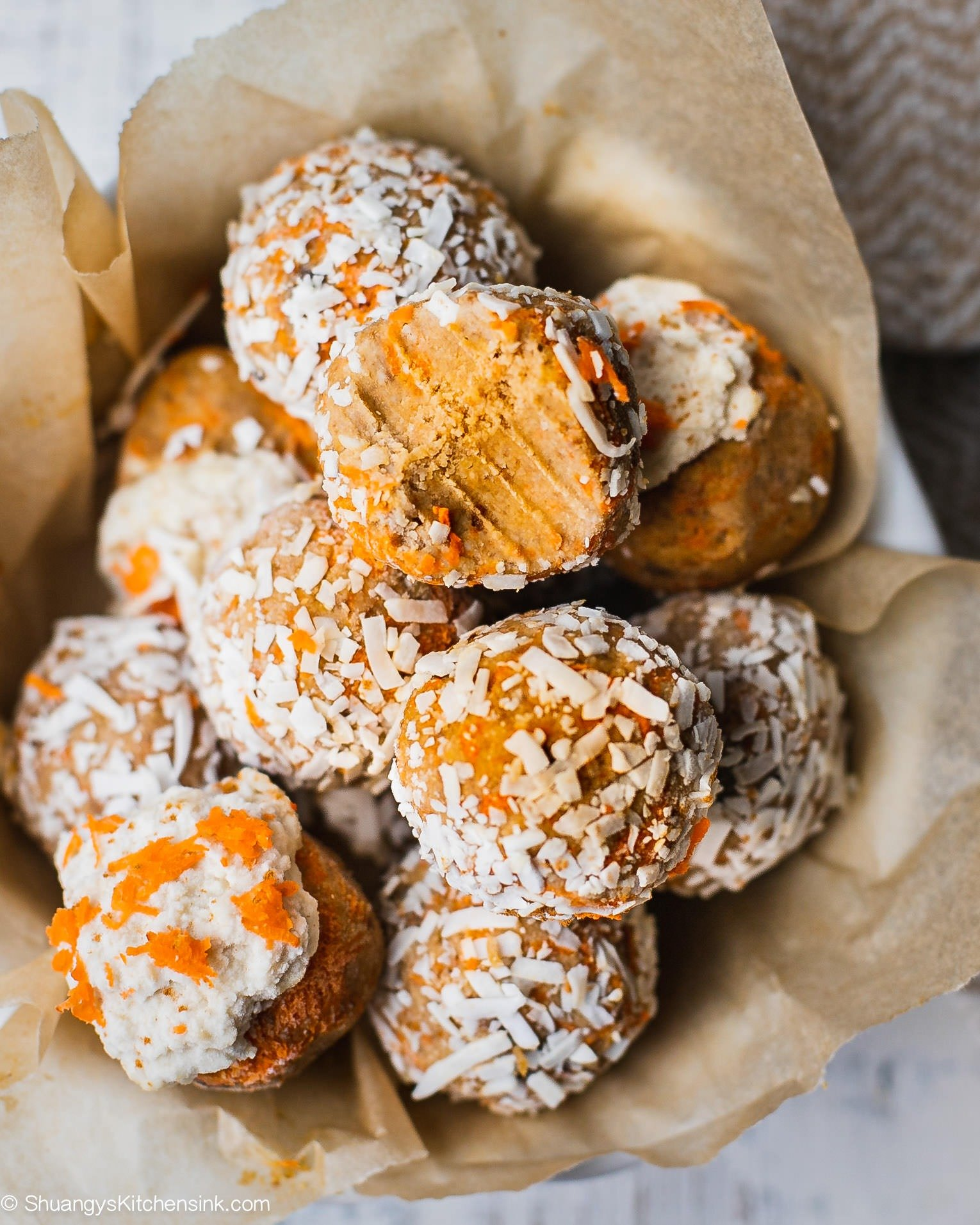 There is a pile of gooey and fudgy energy balls that are rolled in shaved coconut