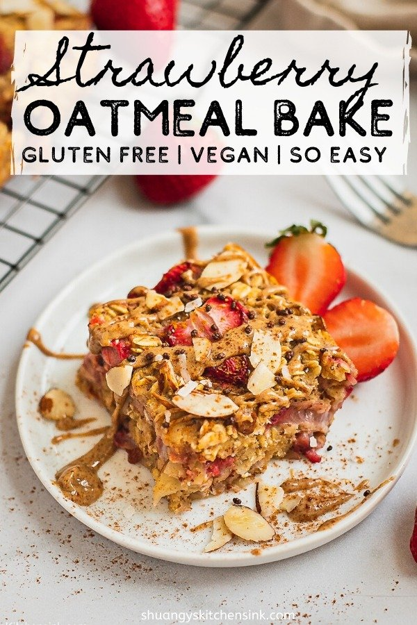 A square of strawberry bake oatmeal topped with almond butter and strawberry, sliced almonds. There are some fresh strawberries in the background and a fork. Pinterest Image