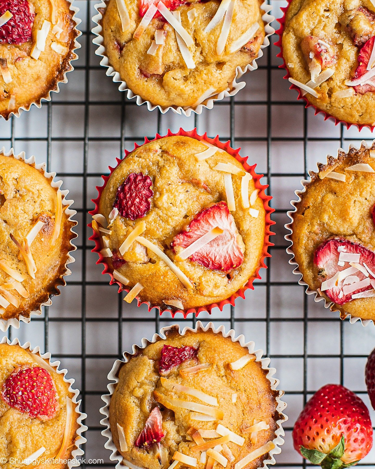 A batch of freshly baked strawberry muffins on a cooling rack. There are a few pieces of fresh strawberries on the side.