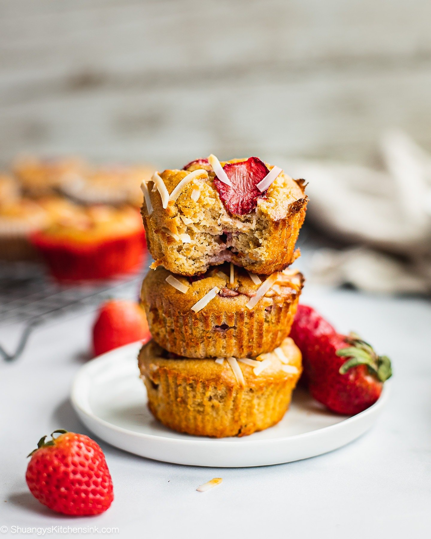There is a stack of strawberry banana muffin on a plate, topped with nut butter, fresh strawberry. There is a bite.
