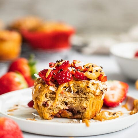 There is a strawberry banana muffin on a plate, topped with nut butter, fresh strawberry. There is a bite.