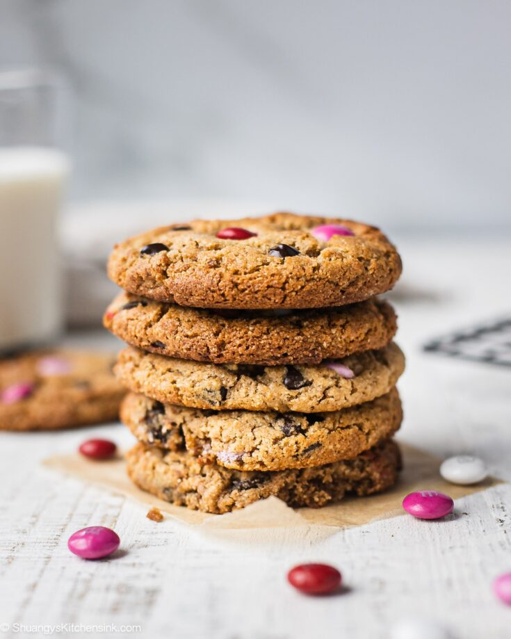 A stack of eggless chocolate chip cookies with M&M that can be made keto, and paleo as well. Perfect for a healthy Valentine's Day dessert. There are a few pink M&Ms on the table and a glass of milk in the background to serve the cookies with.