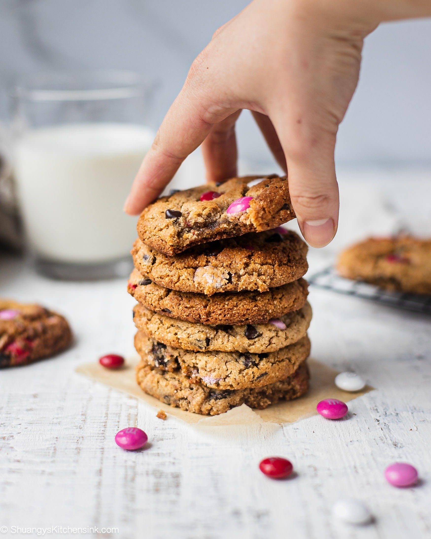 A stack of eggless chocolate chip cookies with M&Ms that can be made vegan, keto and paleo. Perfect healthy cookies for Valentine's Day. A hand is reaching to grab the top eggless chocolate chip cookies. There are extra M&Ms on the table.