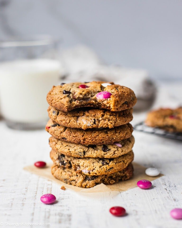 A stack of eggless chocolate chip cookies with M&Ms that can be made vegan, keto and paleo. Perfect healthy cookies for Valentine's Day. There are extra M&Ms on the table.