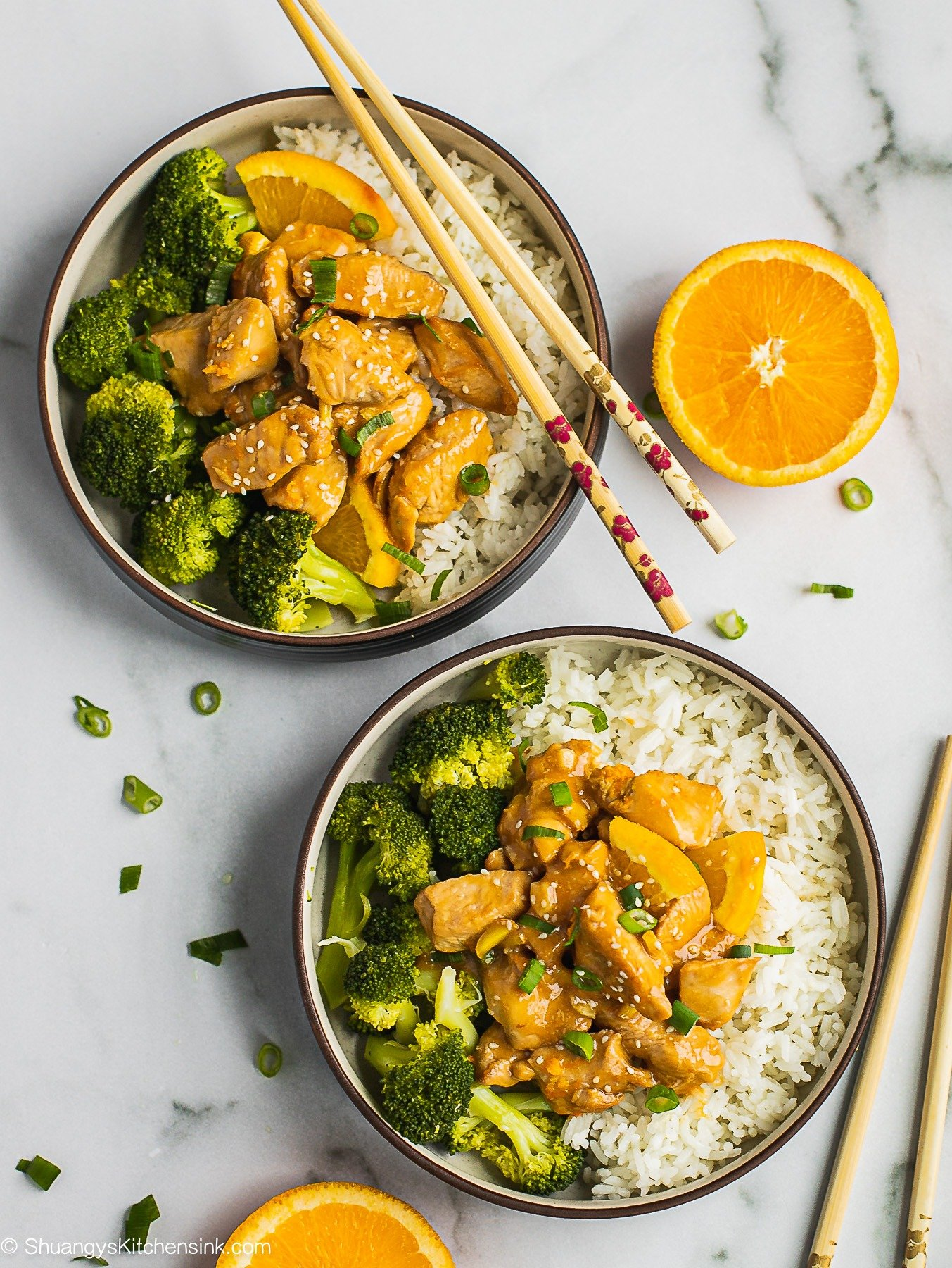 Two bowls of paleo orange chicken over rice and steamed broccoli. There is a pair of chopsticks on the bowl. There are a piece of orange slice in on the table.