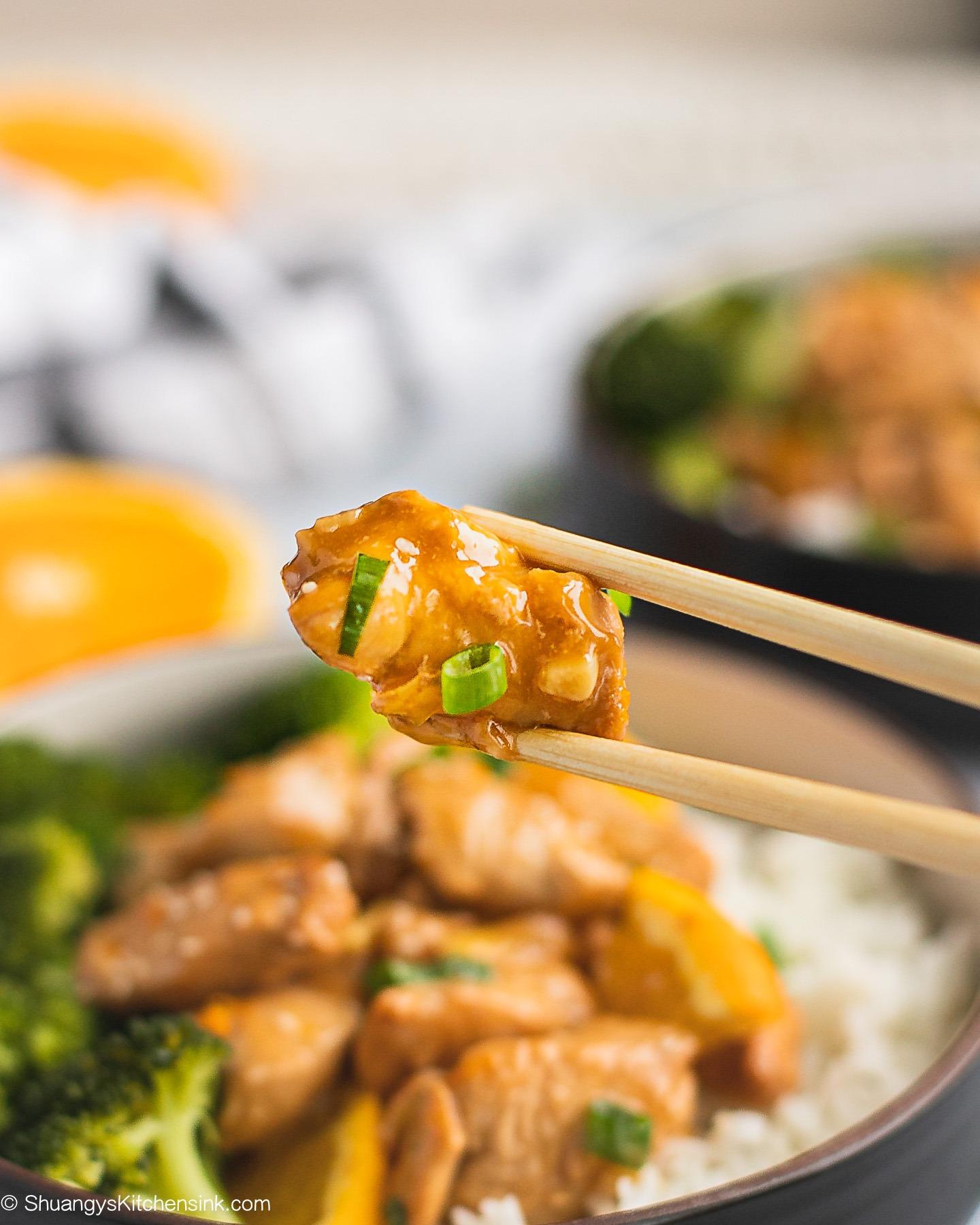 A pair of chopsticks picking up a piece of orange chicken.