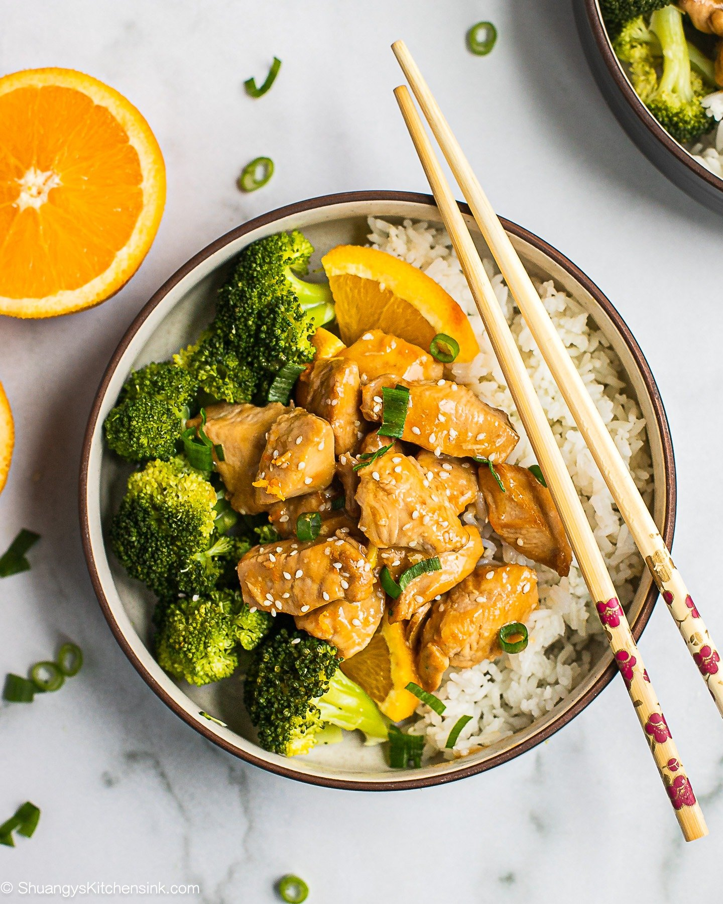 A bowl of paleo orange chicken over rice and steamed broccoli. There is a pair of chopsticks on the bowl.