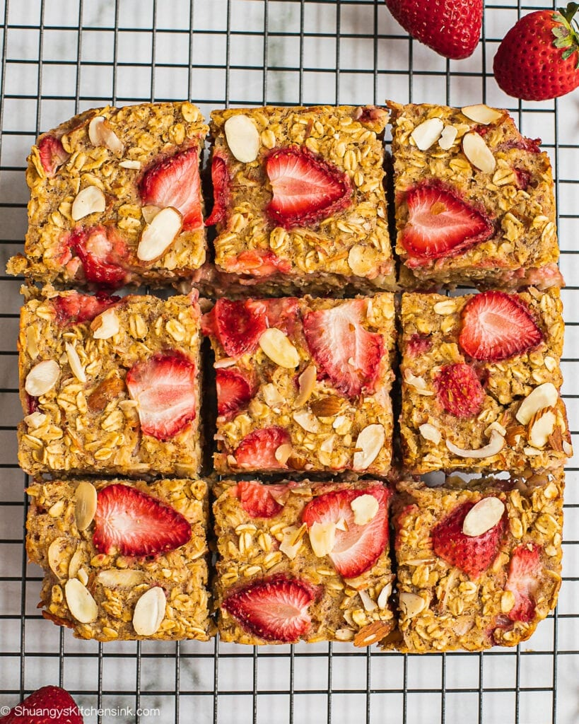 Freshly baked and cut strawberry oatmeal bake on a cooling wrap. There are fresh strawberry and sliced almonds on top.