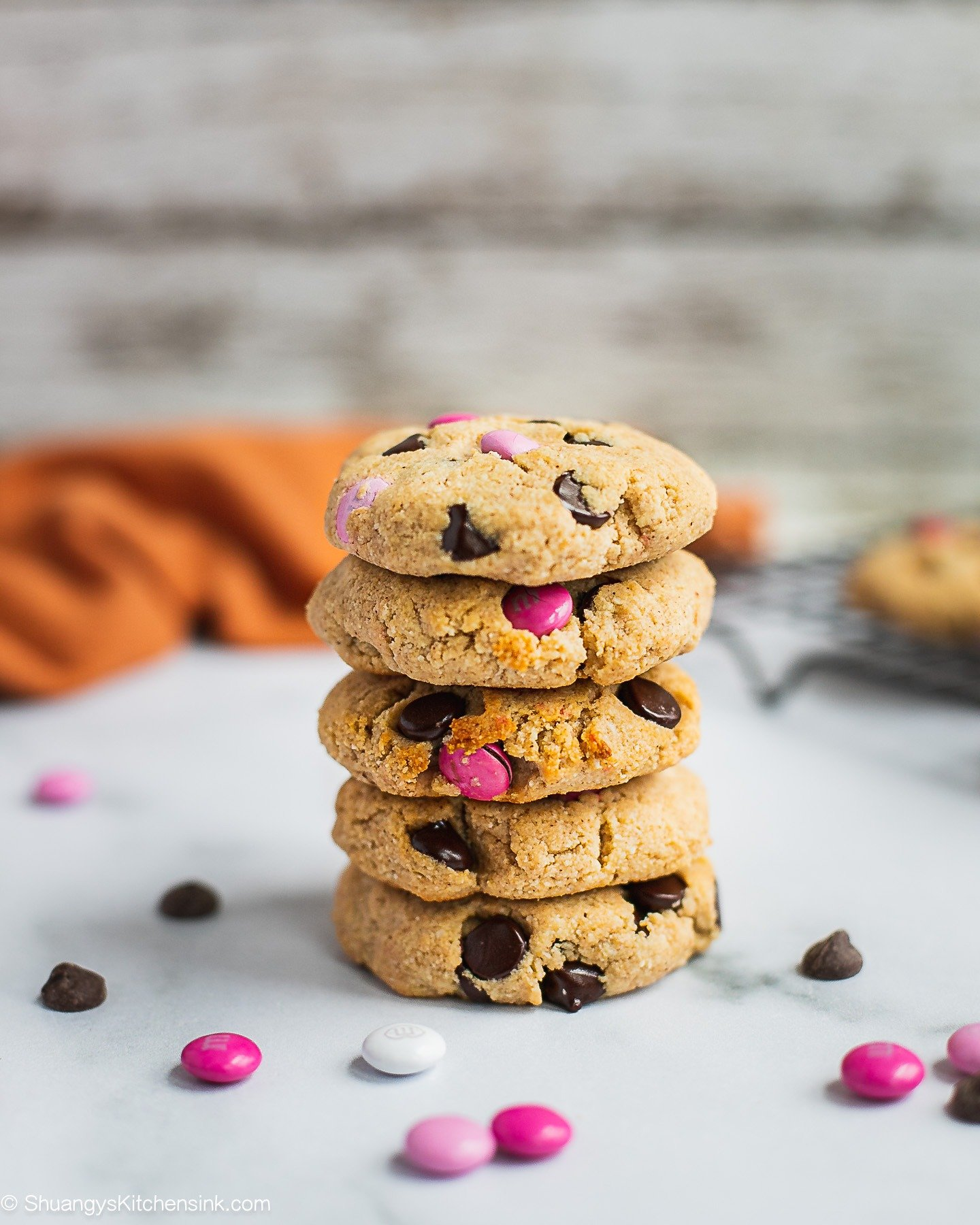 A stack of chocolate chip M&M cookies. There are pieces of M&Ms around it and an orange towel in the back.