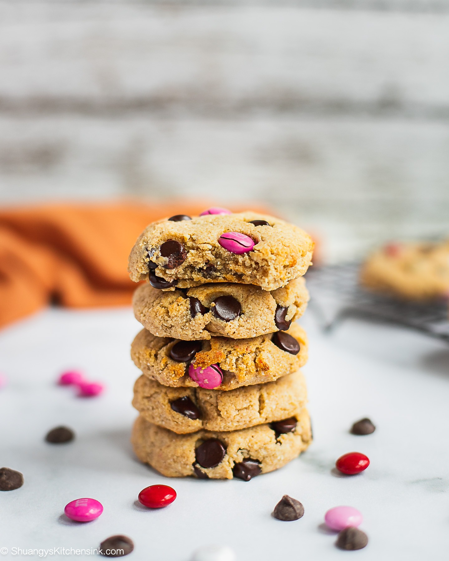 A stack of chocolate chip M&M cookies. There are pieces of M&Ms around it and an orange towel in the back. There is a bite in the cookie on top.