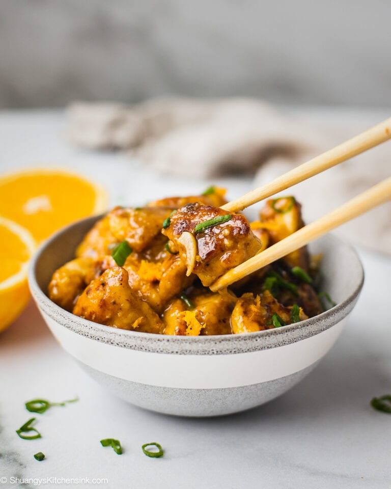 A bowl fo whole30 orange chicken ready to be served. The healthy orange chicken is juicy and tender, coated with tangy orange sauce. There is a pair of chopsticks.