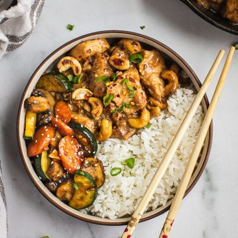 A bowl of cashew chicken and stir fried veggies and a side of jasmine rice.
