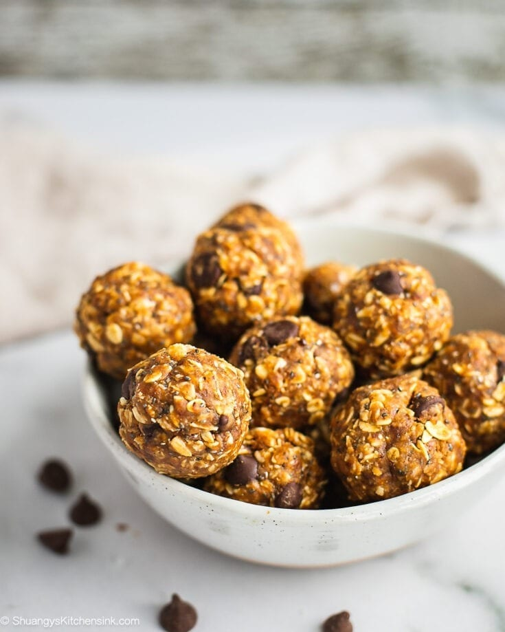 A plate of peanut butter oatmeal balls. There are a few chocolate chips on the plate and table.