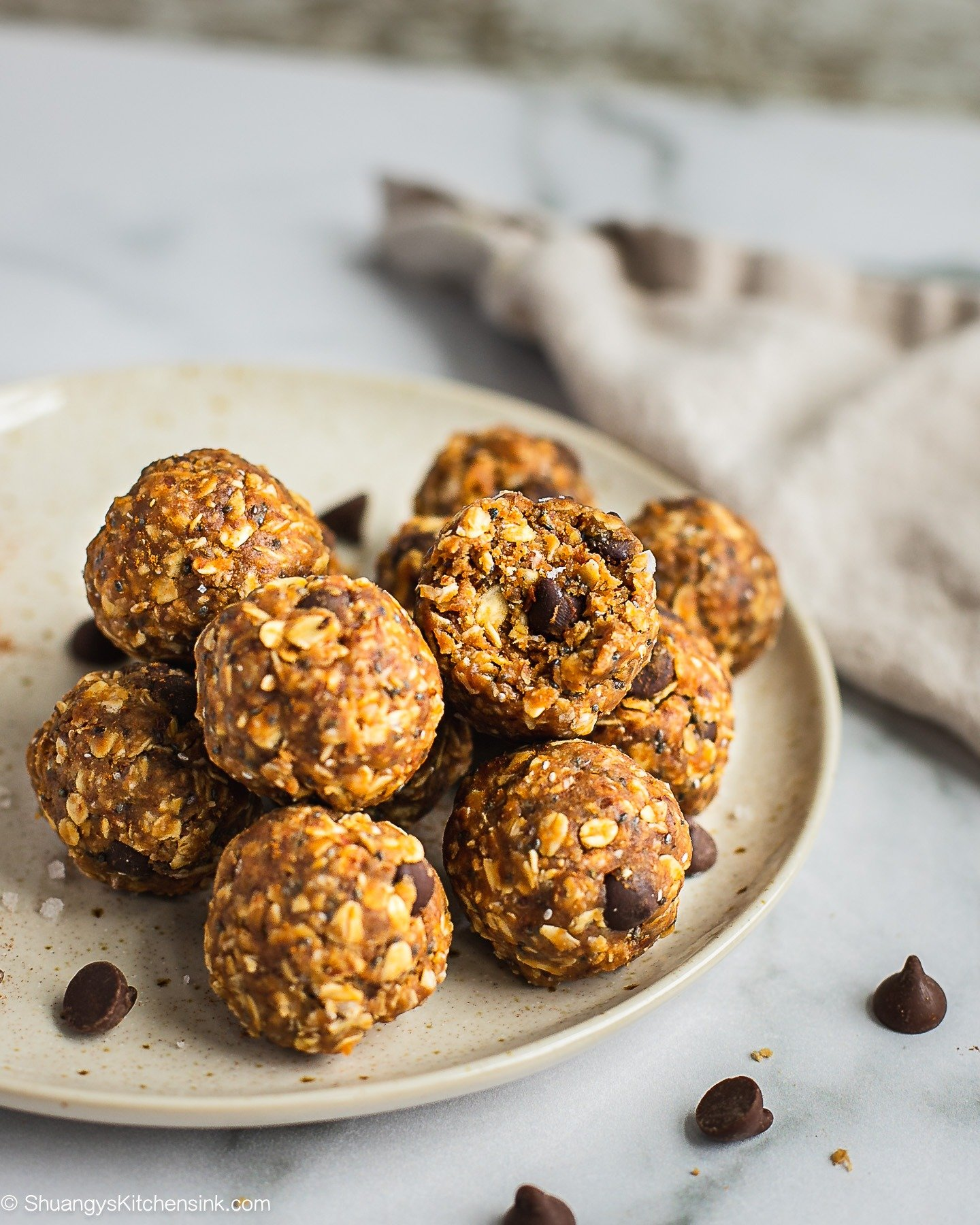 A plate of peanut butter oatmeal balls. There is a bite on the top one. There are a few chocolate chips on the plate and table.