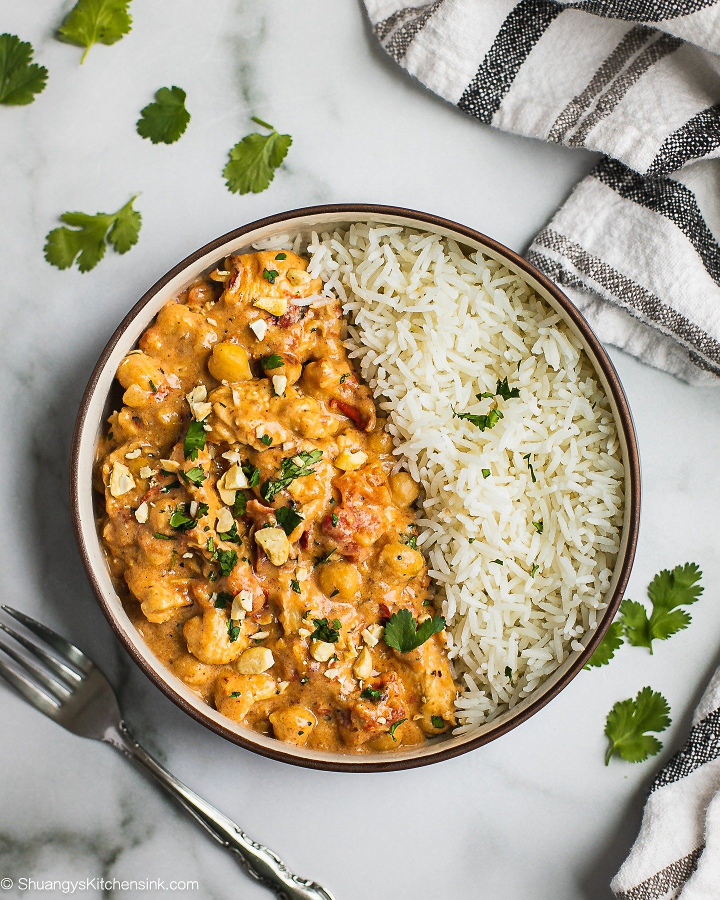 A bowl of creamy peanut butter chicken served with white rice and fresh cilantro. There are some crushed cashews on top.