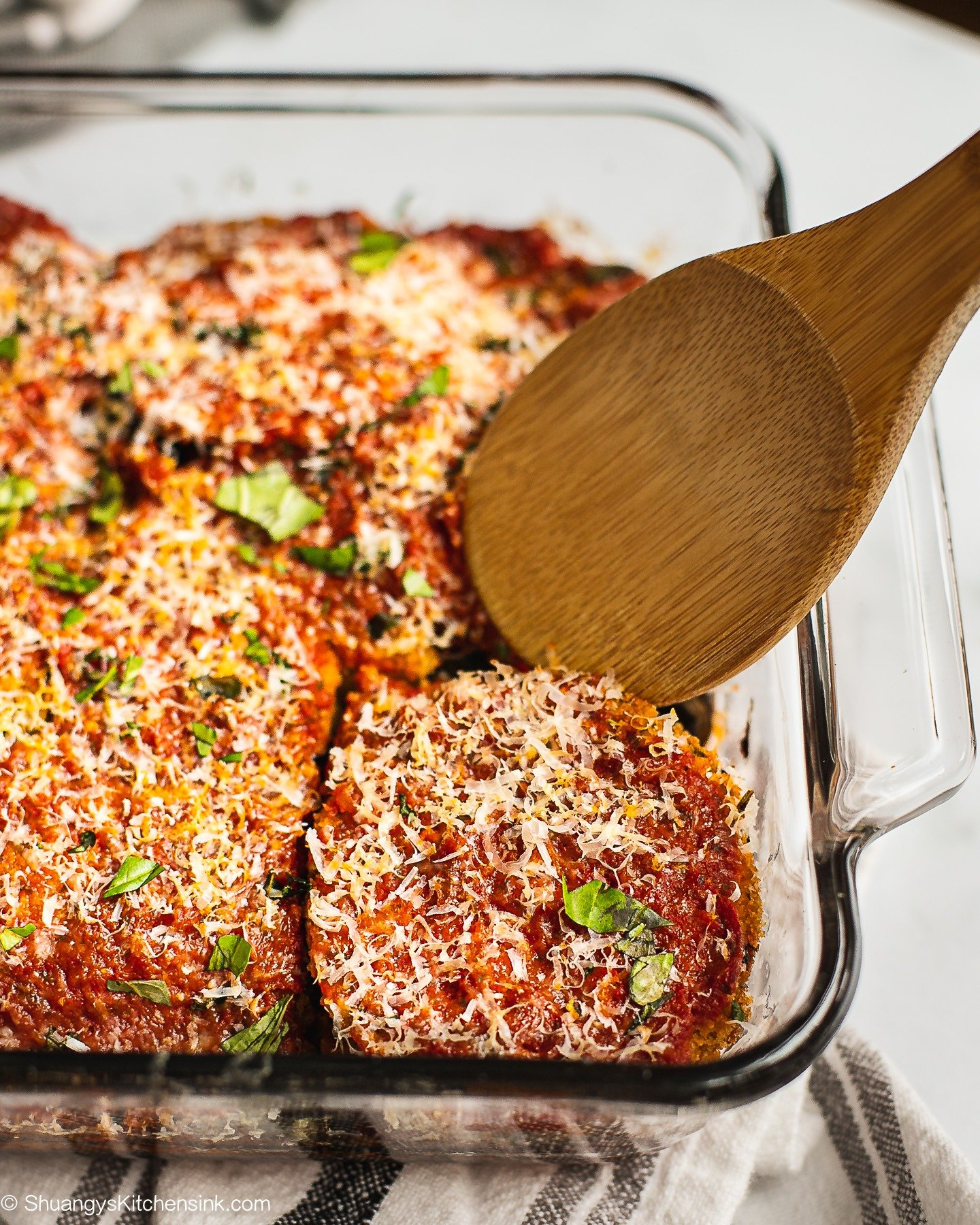 Freshly Bake Eggplant Parmesan just came out of the oven. There is a spoon holding up one piece.