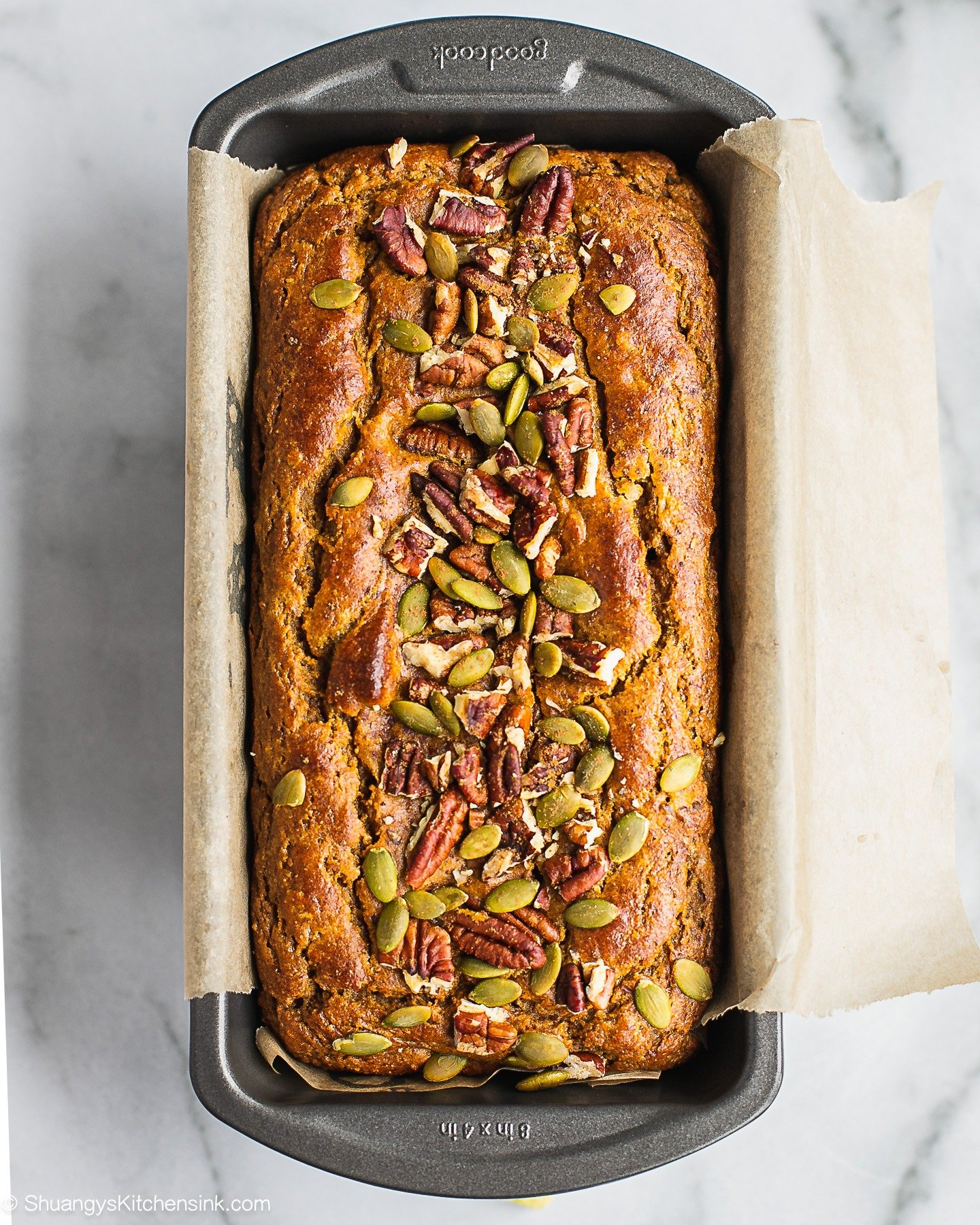 Instructions on how to make sweet potato bread step by step. A loaf of freshly baked healthy bread topped with pecans and pumpkin seeds.
