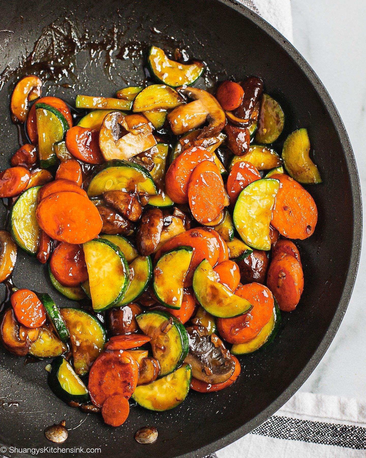 A pan full of mushrooms, carrots and zucchini coated in a a brown sauce.