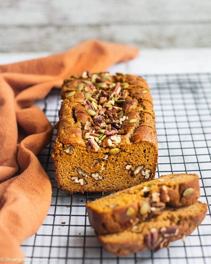 A loaf of sweet potato bread on a cooling rack. There are sprinkles of pumpkin seeds and pecans on top.