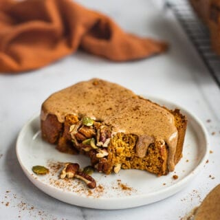A slice of paleo sweet potato bread on a plate. It is topped with nut butter and cinnamon. there is a cooling rack and the rest of the loaf in the back.