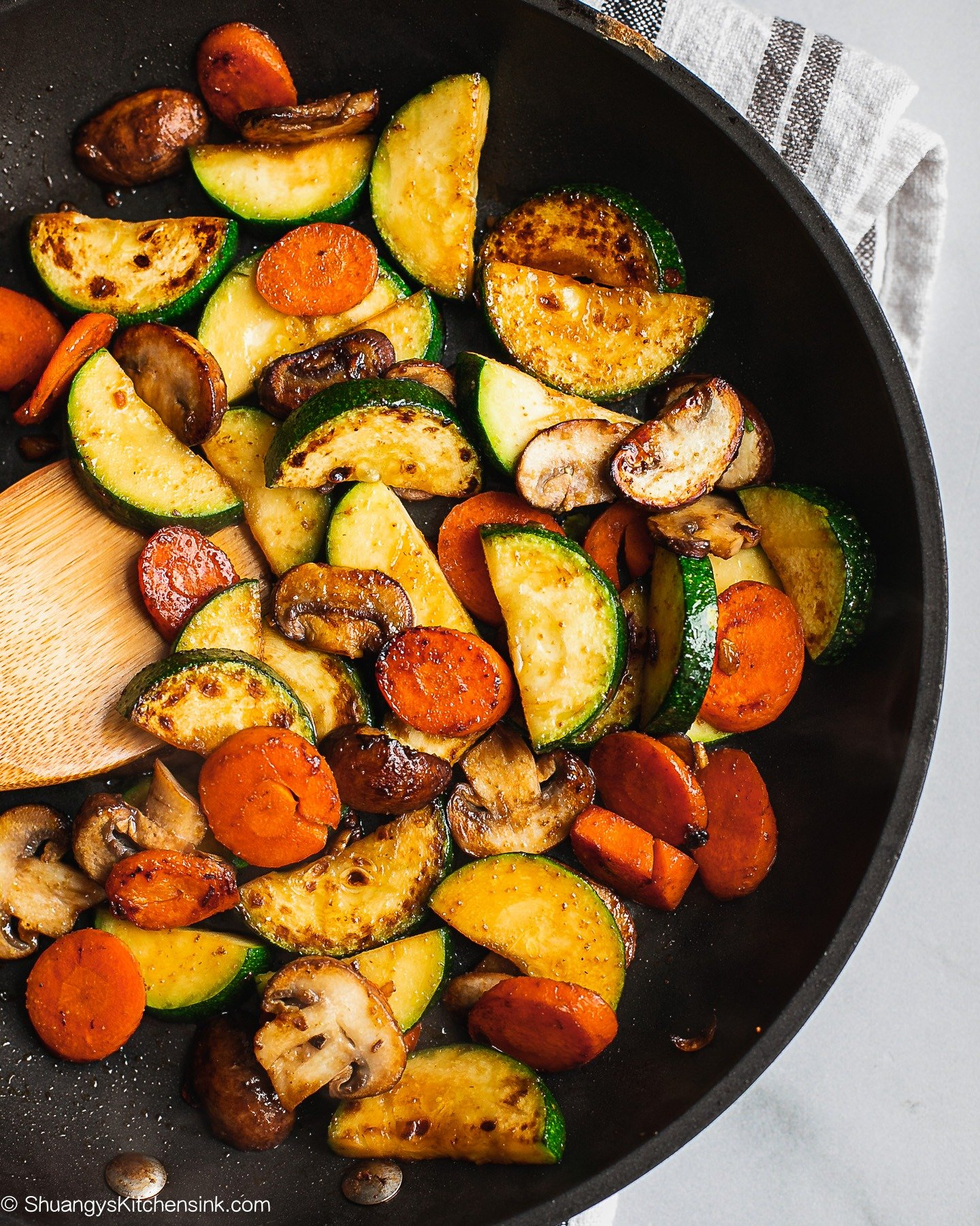 A pan of Zucchini Mushroom Stir Fry. There are zucchini, mushroom, and carrots in them.