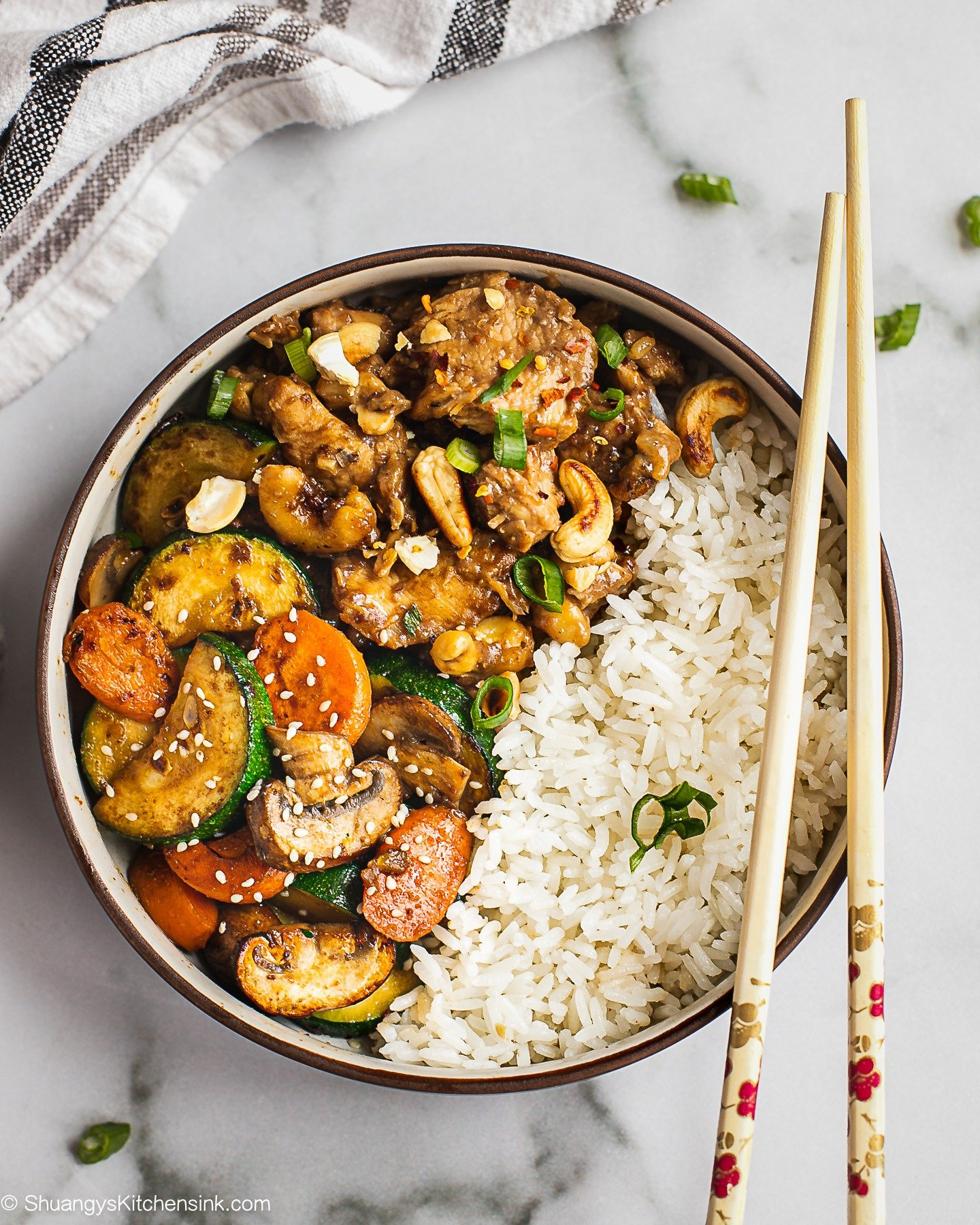 A bowl of Jasmin rice and stir fried zucchini, carrots and mushrooms. There are also chop sticks.