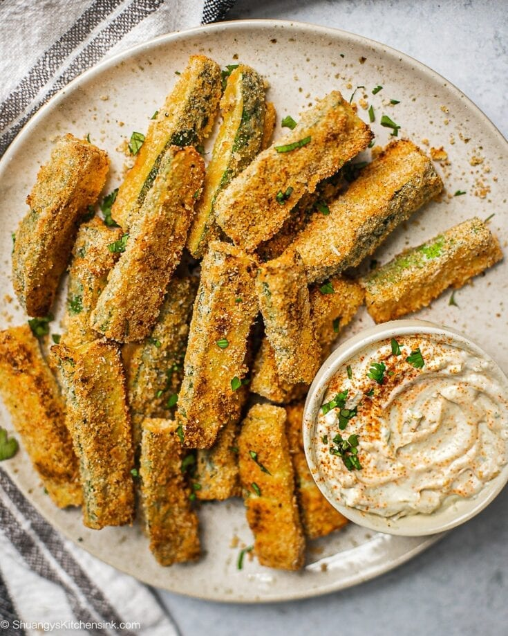 A plate of zucchini fries on a plate. There is a serving dish with garlic aioli.