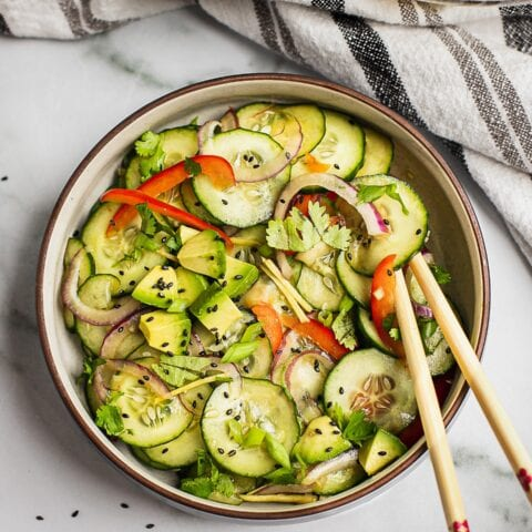 A bowl of asian cucumber salad. There are cucumbers, red bell pepper, red onion and black sesame seeds.