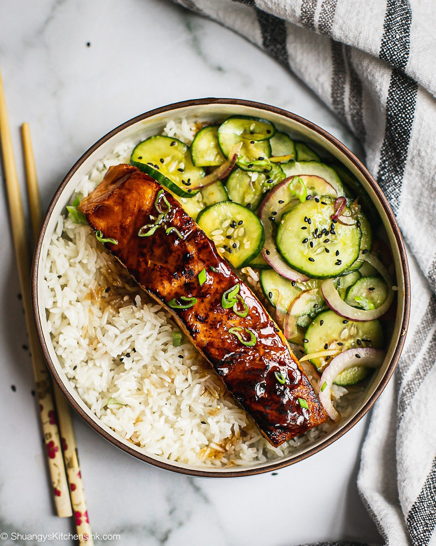 A bowl of jasmine rice crispy teriyaki salmon, asian cucumber salad. There is a pair of chopsticks on the side.
