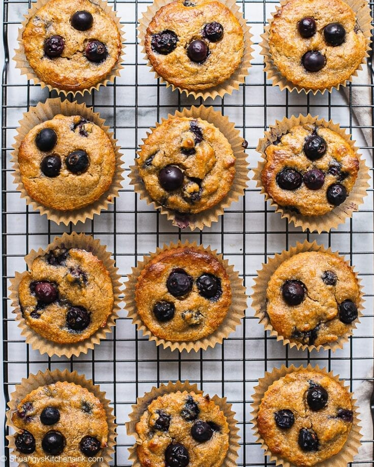 A dozen of healthy blueberry muffins on a cooling rack.