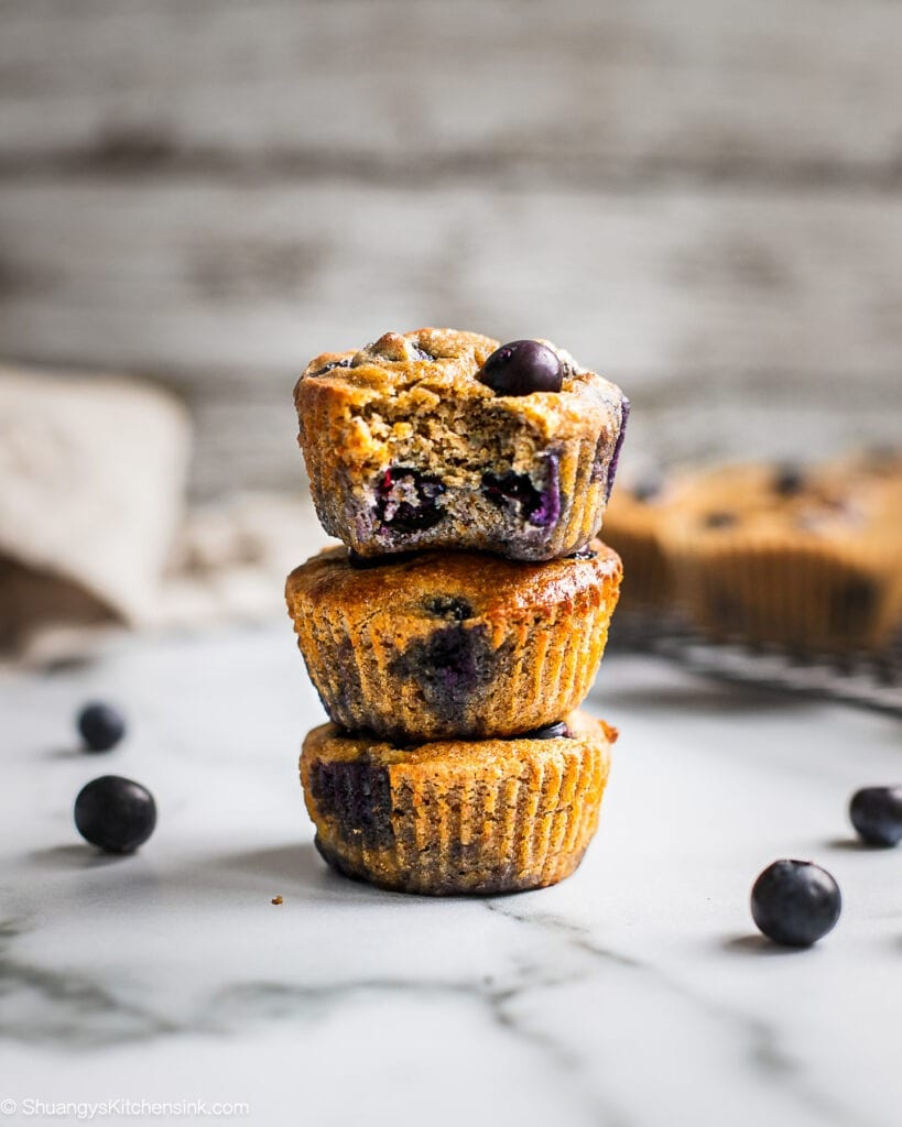 A stack of three blueberry banana muffins. There are a few blueberries on the side. There are more blueberries the back.