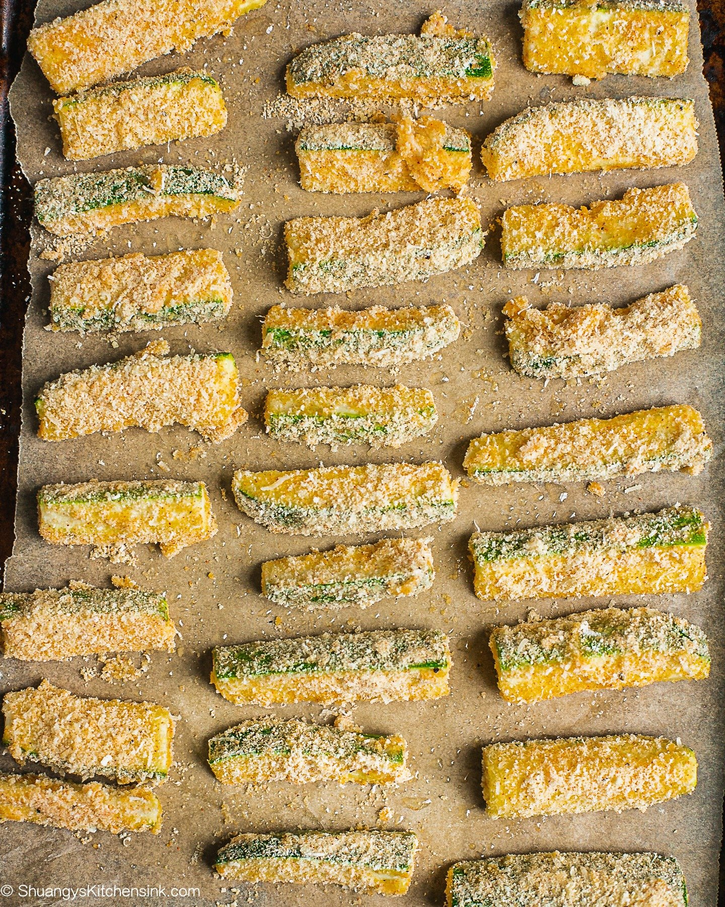 Coated zucchini fries on a baking tray ready to hit the oven